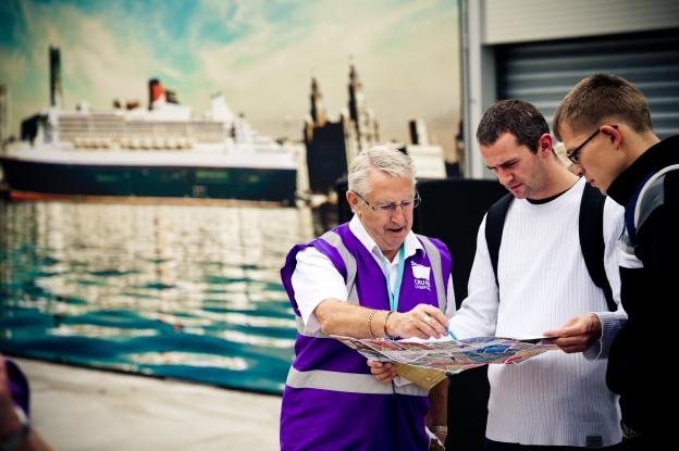 cruise liverpool ambassador giving instructions to two passengers looking at a map