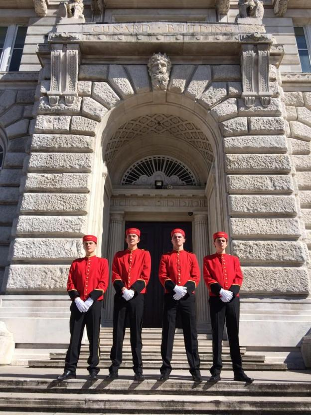 four bell boys standing outside the main doors to cunard building