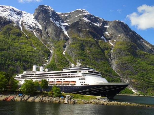 Fred Olsen cruise vessel on the water with a backgdrop of mountains and a blue sky